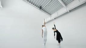 Dziewczyna w bielu i facet w czarnych baletniczych tancerzach pięknie tanczymy w białym balet klasy 20s 1080p zwolnionym tempie zbiory wideo
