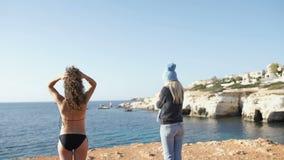 Dziewczyna w bikini i dziewczyna śmia się przy each inny przed oceanem w ciepłych ubraniach zbiory