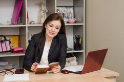 Dziewczyna w biura ze złością spojrzeniach notatnik Obraz Stock