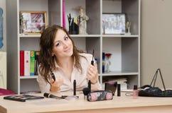 Dziewczyna w biurze wybiera uzupełniał niektóre tusz do rzęs rzęsy Zdjęcie Stock