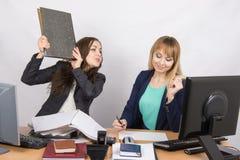 Dziewczyna w biurze zagraża uderzać innego skoroszytowego pracownika Zdjęcia Royalty Free