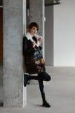 Dziewczyna w brown futerkowym żakiecie pozuje na tle ściana czerwona cegła Obrazy Stock
