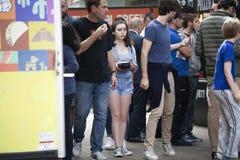 Dziewczyna w cajgów skrótach z pudełkiem jedzenie gramoli się przez tłumu Obrazy Royalty Free
