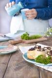 Dziewczyna w cajgów ubraniach przygotowywa lunch bekon i ciasto, z świeżymi ziele brązowe drewniane tła Kramic naczynia błękitny  obraz royalty free