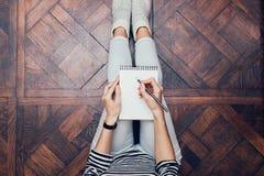 Dziewczyna w cajgach siedzi w domu na podłoga i pisze z a obrazy royalty free