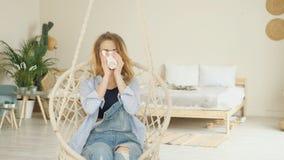 Dziewczyna w cajgach siedzi w wieszać łozinowego krzesła pije kawę zbiory wideo