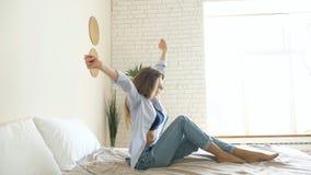 Dziewczyna w cajgach siedzi z ciekami na łóżku rozciąga za rękach zdjęcie wideo