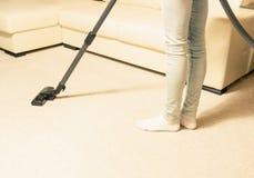 Dziewczyna w cajgach vacuuming dom Jaskrawy dywan fotografia royalty free