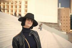 Dziewczyna w czarnego kapeluszu i kurtki pozie na schodkach zdjęcie stock
