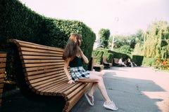 Dziewczyna w czarnej koszula i skrótach w parku na ławce zdjęcia stock