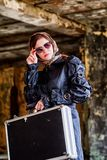 Dziewczyna w czarnej pelerynie, szaliku i dyplomacie w zaniechanym domu, Szpieg w tajnym spotkaniu obrazy royalty free