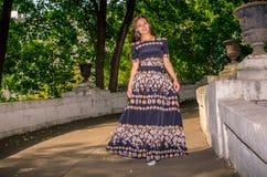 Dziewczyna w czarnej pstrobarwnej sukni biega przez most Obrazy Stock