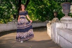 Dziewczyna w czarnej pstrobarwnej sukni biega przez most Obrazy Royalty Free