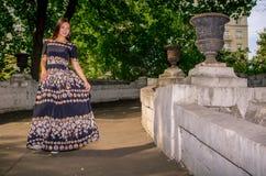 Dziewczyna w czarnej pstrobarwnej sukni biega przez most Obraz Royalty Free