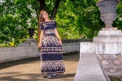 Dziewczyna w czarnej pstrobarwnej sukni biega przez most Zdjęcie Stock