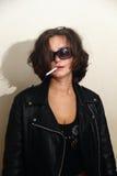 Dziewczyna w czarnych skórzanych kurtkach z papierosem i. Obrazy Royalty Free