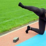 Dziewczyna w czarnych spodniach wykonuje sportów ćwiczenia w stadium Mięśnia rozciąganie i szkolenie Noga podnosi up jak pies fotografia stock