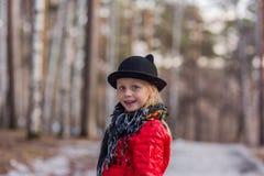 Dziewczyna w czarnym kapeluszu z ucho i Pavloposadskiye szalikiem chodzi w parkowym zimnym wiosna dniu Obrazy Stock