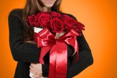 Dziewczyna w czarnym kurtki mieniu w ręka prezenta bogatym bukiecie 21 czerwień Obraz Stock