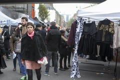 Dziewczyna w czarnym sztucznym futerkowym żakiecie wybiera ja odzieżowy w ulicznym rynku Obrazy Royalty Free