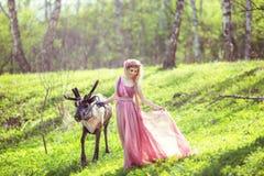Dziewczyna w czarodziejki sukni z bieżącym pociągiem smokingowy odprowadzenie z reniferem Zdjęcia Royalty Free
