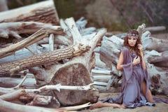 Dziewczyna w czarodziejskiego światła sukni siedzi blisko starych drzew Obrazy Stock