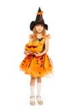 Dziewczyna w czarownicy sukni chwycie rzeźbił Halloweenowej bani Obrazy Stock