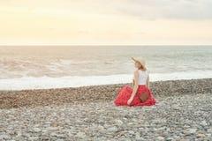 Dziewczyna w czerwień kapeluszu i spódnicie siedzi na seashore ujawnienia zawodnik bez szans zmierzchu czas bac Zdjęcie Royalty Free