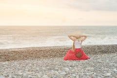Dziewczyna w czerwień kapeluszu i spódnicie siedzi na seashore ujawnienia zawodnik bez szans zmierzchu czas bac Obraz Royalty Free