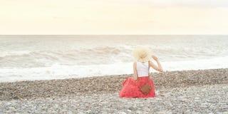 Dziewczyna w czerwień kapeluszu i spódnicie siedzi na seashore ujawnienia zawodnik bez szans zmierzchu czas bac Obraz Stock
