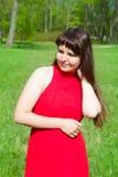 Dziewczyna w czerwieni i zielonej zielonej trawie Obrazy Royalty Free
