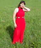 Dziewczyna w czerwieni i zielonej zielonej trawie Fotografia Stock