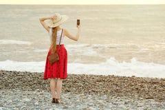 Dziewczyna w czerwieni spódnicie robi selfie na plaży na tle kapeluszu i morza i nieba widok z powrotem Obrazy Stock