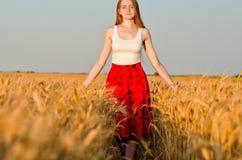 Dziewczyna w czerwieni spódnicy odprowadzeniu na pszenicznym polu Obrazy Royalty Free