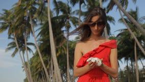 Dziewczyna w czerwieni sukni blisko drzewek palmowych Ona cieszyć się frangipani kwiaty zdjęcie wideo