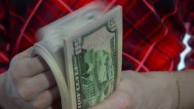 Dziewczyna w czerwieni sukni liczy paczkę pieniądze w rękach w zwolnionym tempie zbiory wideo