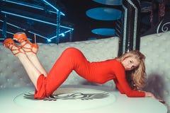 Dziewczyna w czerwieni sukni na stole Obraz Royalty Free