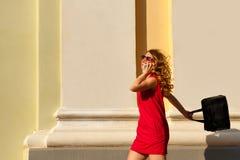 Dziewczyna w czerwieni sukni z modną torebką i obraz stock