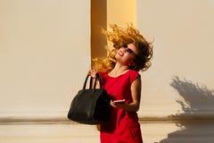 Dziewczyna w czerwieni sukni z modną torebką i, telefon obrazy stock