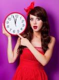 Dziewczyna w czerwieni sukni z ogromną zegarowej tarczy twarzą Obrazy Stock