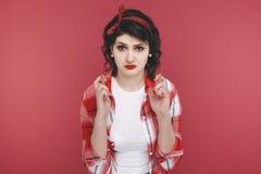 Dziewczyna w czerwieni ubraniach krzyżował ona palce w nadziei odizolowywającej w studiu zdjęcia stock