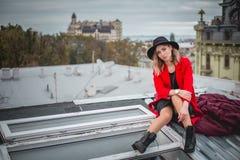 Dziewczyna w czerwieni z czarnym kapeluszem pozuje na dachu stary miasto i obrazy royalty free