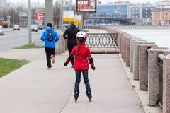 Dziewczyna w czerwonej kurtce i niebieskich dżinsach rollerblading fotografia stock
