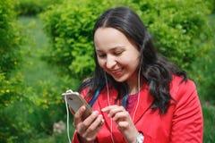 Dziewczyna w czerwonej kurtce w Parkowym słuchaniu muzyka z hełmofonów earbuds z smartphone w ręce obraz royalty free