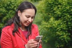 Dziewczyna w czerwonej kurtce w Parkowym s?uchaniu muzyka z he?mofon?w earbuds z smartphone w r?ce zdjęcia royalty free