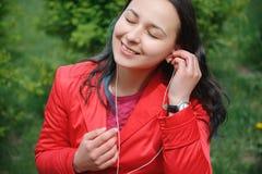 Dziewczyna w czerwonej kurtce w Parkowym s?uchaniu muzyka z he?mofon?w earbuds z smartphone w r?ce zdjęcie stock