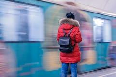 Dziewczyna w czerwonej kurtce z plecaka stojakami z ona na t z powrotem Obraz Royalty Free