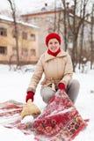 Dziewczyna w czerwonej nakrętce czyści dywan z śniegiem obraz stock