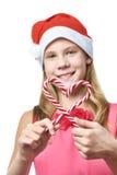 Dziewczyna w czerwonej nakrętce z boże narodzenie cukierku trzcinami jako serce odizolowywający Zdjęcie Royalty Free