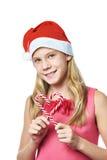 Dziewczyna w czerwonej nakrętce z boże narodzenie cukierku trzcinami jako serce odizolowywający Obraz Royalty Free